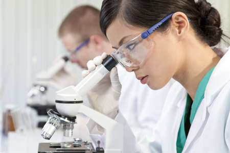 medical laboratory: A Chinese Asian female medical or scientific researcher or doctor using a microscope in a laboratory with her colleague out of focus behind her.