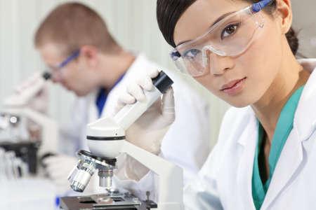 investigador cientifico: Un chino, asi�tico, investigadora m�dica o cient�fica o el m�dico utiliza un microscopio en un laboratorio con su colega fuera de foco detr�s de ella.