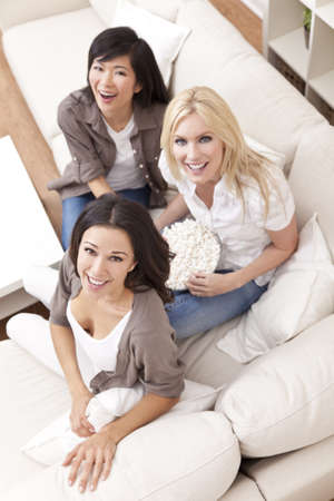 three women: Three beautiful young women friends at home eating popcorn watching a movie together and laughing Stock Photo
