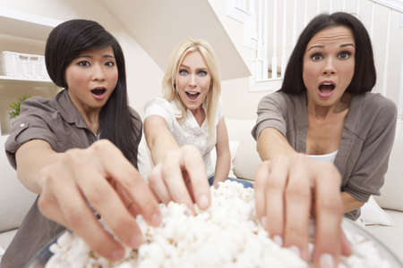 Three beautiful young women friends at home eating popcorn watching a movie together and looking shocked or surprised photo