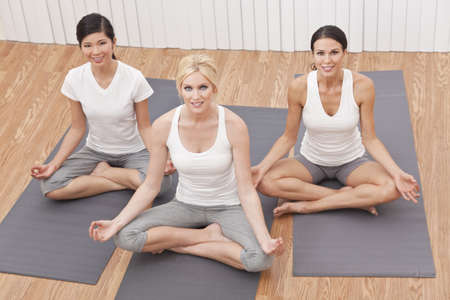 An interracial group of three beautiful young women sitting cross legged in a yoga position at a gym Stock Photo - 11148406