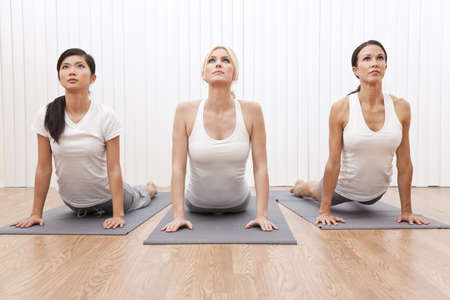 An interracial group of three beautiful young women stretching in a yoga position at a gym photo