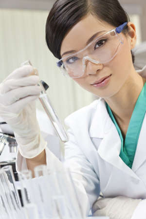 chemist: A Chinese Asian female medical or scientific researcher or doctor using looking at a test tube of clear liquid in a laboratory with her colleague out of focus behind her. Stock Photo