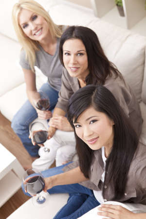 Interracial group of three beautiful young women friends at home drinking red wine together photo