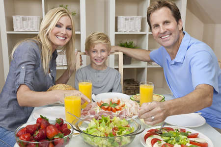 An attractive happy, smiling family of mother, father and son eating salad and healthy food at a dining table photo