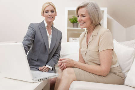 advising: A young saleswoman showing a senior woman medical insurance or pension information on a laptop computer