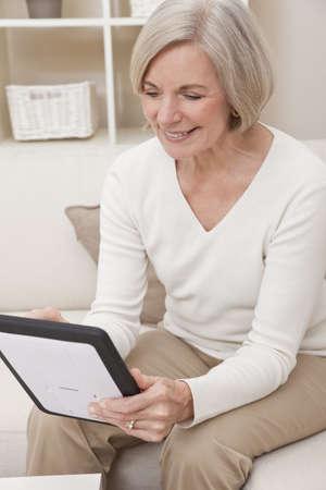 Attractive elegant senior woman using a tablet computerat home.