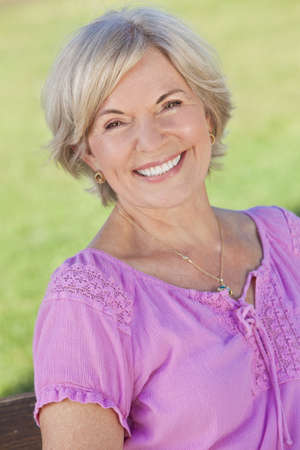 Happy senior woman sitting outside and smiling photo