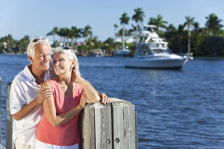 wealthy lifestyle: Happy senior man and woman couple together by a river or sea in a tropical location with a boat sailing past
