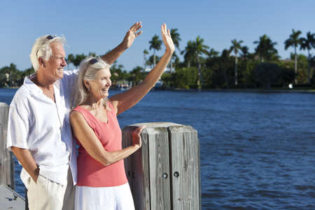 goodbye: Happy senior man and woman couple together outside in sunshine waving by the sea on a jetty or pier