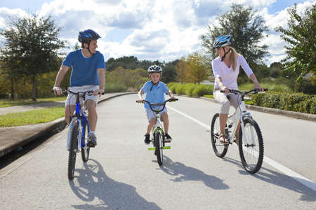 one family: A young family of man and woman parents and one boy child, cycling together.