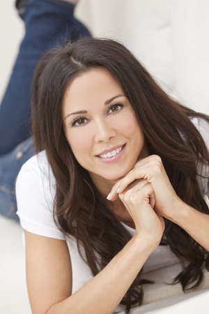 Portrait of a beautiful brunette young woman in jeans and t-shirt smiling laying on her sofa at home photo