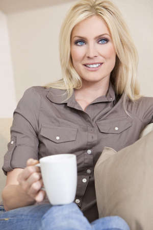 settee: A beautiful young blond woman drinking tea or coffee from a white mug sitting at home on a her sofa
