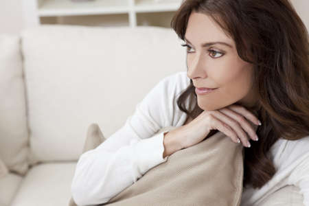 settee: Beautiful smiling brunette woman at home sitting on sofa or settee holding a cushion and thinking