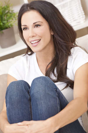 Portrait of a beautiful brunette young woman in jeans and t-shirt smiling siting on her sofa at home photo