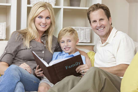 An attractive happy, young family of mother, father and son sitting on a sofa at home looking at a photo album photo