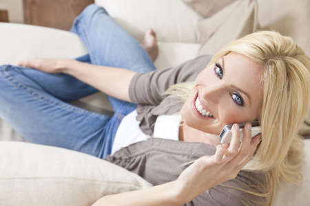 Overhead photograph of beautiful young woman at home sitting on sofa or settee using her cell or mobile phone and smiling Stock Photo - 11274476