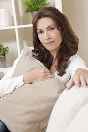 Beautiful brunette woman at home sitting on sofa or settee holding a cushion and thinking Stock Photo