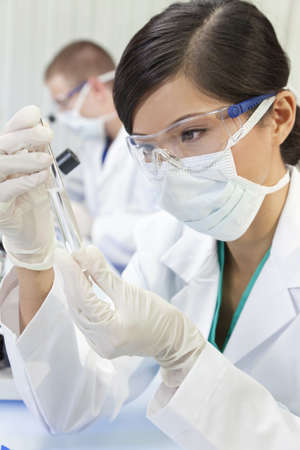 A Chinese Asian female medical or scientific researcher or doctor using looking at a test tube of clear liquid in a laboratory with her colleague out of focus behind her. photo