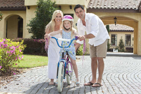 A young family with girl child riding a bicycle and her happy parents giving encouragement  photo