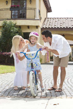 A young family with girl child riding a bicycle and her happy excited parents giving encouragement alongside her photo