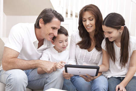 wealthy lifestyle: An attractive happy, family of mother, father, son and daughter sitting on a sofa at home having fun using a tablet computer