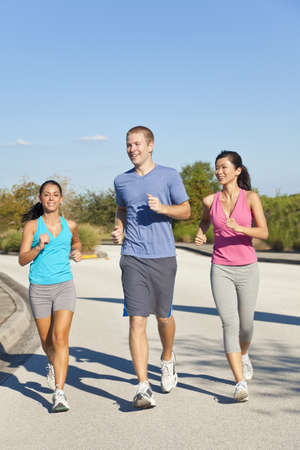 Three fit and healthy interracial young adult friends running or jogging together photo