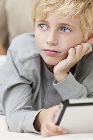 rubia ojos azules: Un joven de pelo rubio niño de ojos azules niño apoyada en las manos que se establecen en un sofá con Tablet PC