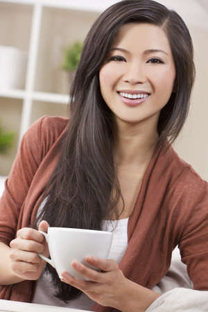 A beautiful young Chinese Asian Oriental woman with a wonderful toothy smile drinking tea or coffee from a white cup and saucer photo