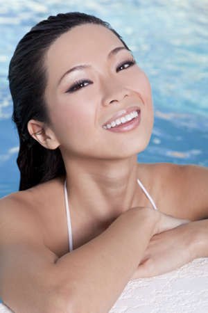 A beautiful sexy young Chinese Asian Oriental woman wearing a bikini and relaxing on the side of a swimming pool. photo