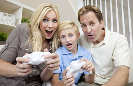 Young family, mother father and son, parents and child, having fun playing video console games together. photo