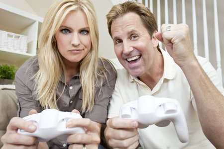 beaten woman: Young married couple, man and woman, having fun playing video console games together. The man has just beaten the woman, he is celebrating, she is unhappy. Stock Photo