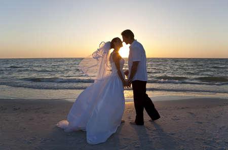結婚されていたカップル、花嫁と花婿、美しい熱帯のビーチの夕日にキス