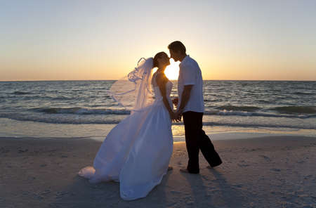 woman beach dress: A married couple, bride and groom, kissing at sunset on a beautiful tropical beach