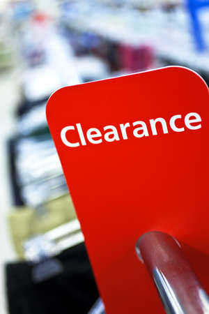 clothes rail: A red sale clearance sign on rail of clothes in a shop