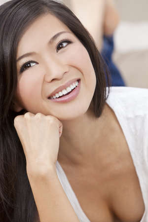 A beautiful young Chinese Asian Oriental woman with a wonderful toothy smile Stock Photo - 12024401