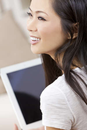 Beautiful Asian Chinese Woman Using Tablet Computer photo