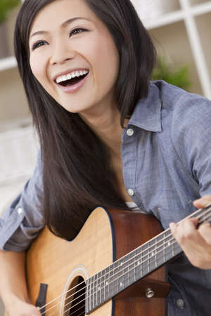 A beautiful happy young Chinese Asian Oriental woman with a wonderful toothy smile holding her guitar  photo