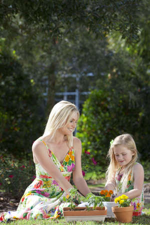 Woman and girl, mother and daughter, gardening together planting flowers and tomato plants in the garden photo