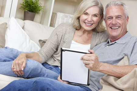 retired couple: Happy senior man and woman couple sitting together at home smiling and happy using a tablet computer Stock Photo