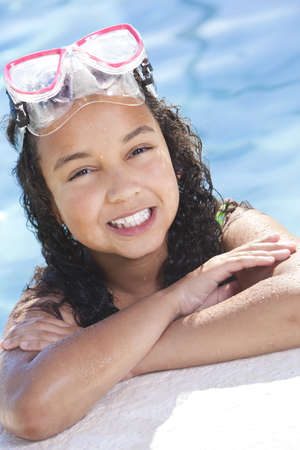 A cute happy young interracial African American girl child relaxing on the side of a swimming pool smiling & wearing pink goggles photo