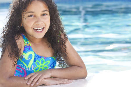 A cute happy young interracial African American girl child relaxing on the side of a swimming pool smiling