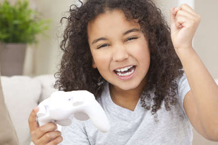 Beautiful young happy mixed race interracial African American girl child celebrating playing video games photo