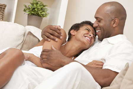 A happy African American man and woman couple in their thirties sitting at home together cuddling & laughing. photo