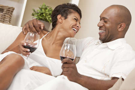 A happy African American man and woman couple in their thirties sitting at home together laughing and drinking glasses of red wine. Stock Photo