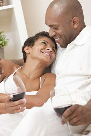 A happy African American man and woman couple in their thirties sitting at home together smiling and drinking glasses of red wine. photo