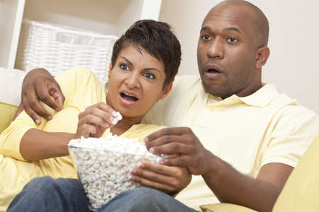 happy african woman: A happy African American man and woman couple in their thirties sitting at home, eating popcorn and looking shocked watching a movie or television Stock Photo