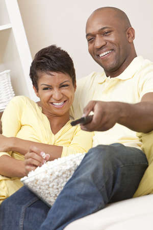 A happy African American man and woman couple in their thirties sitting at home, eating popcorn using remote control watching a movie or television