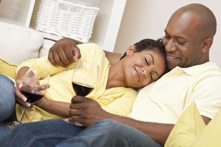 A happy African American man and woman couple in their thirties sitting at home together relaxing and drinking glasses of red wine. photo