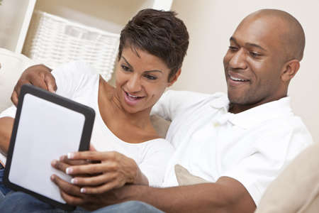african american couple: African American Man Woman Couple Using Tablet Computer
